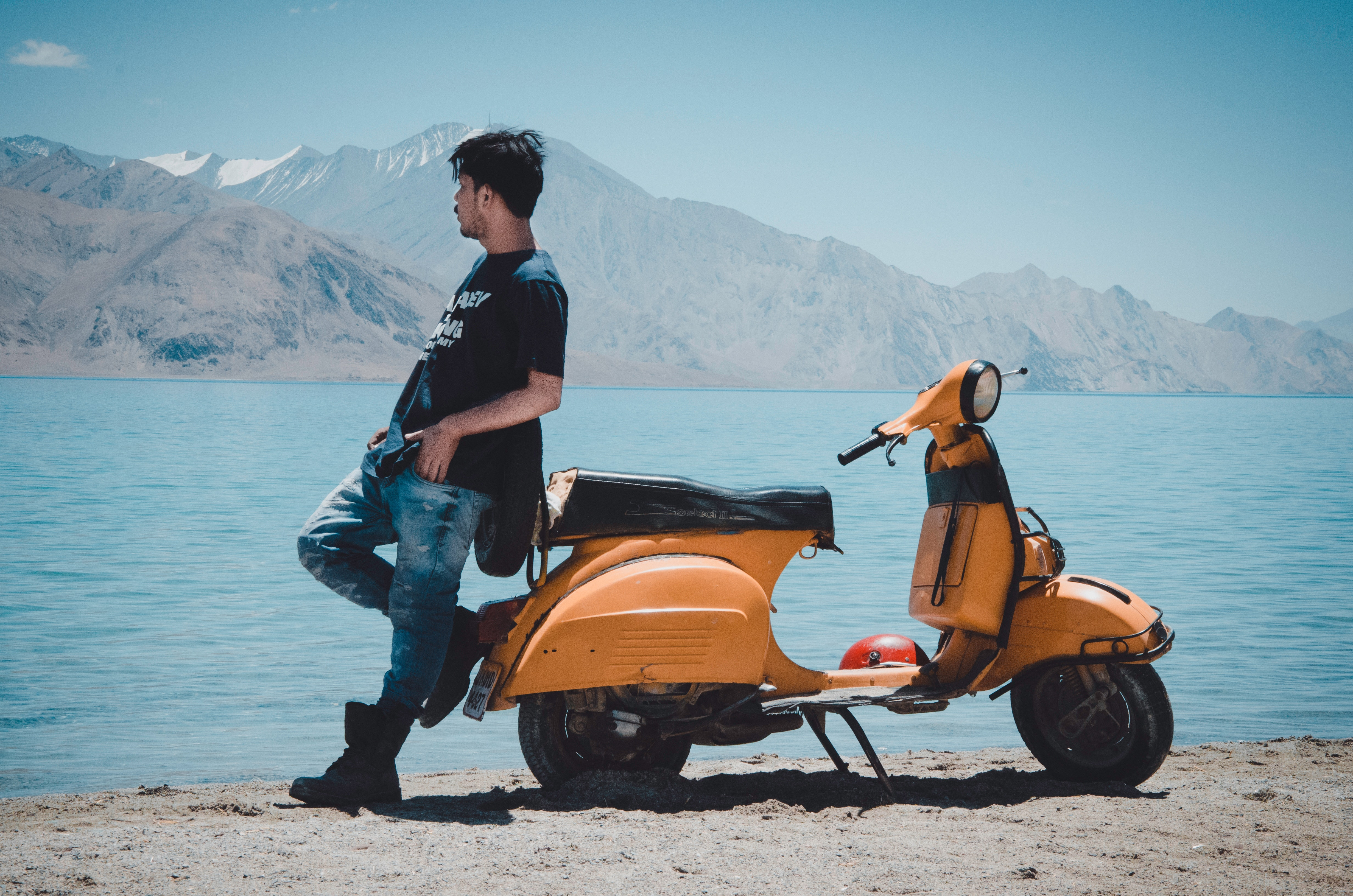 Man leaning against orange scooter in front of ocean