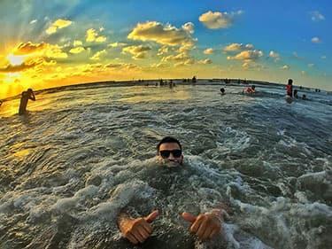 People enjoying calm ocean at sunset