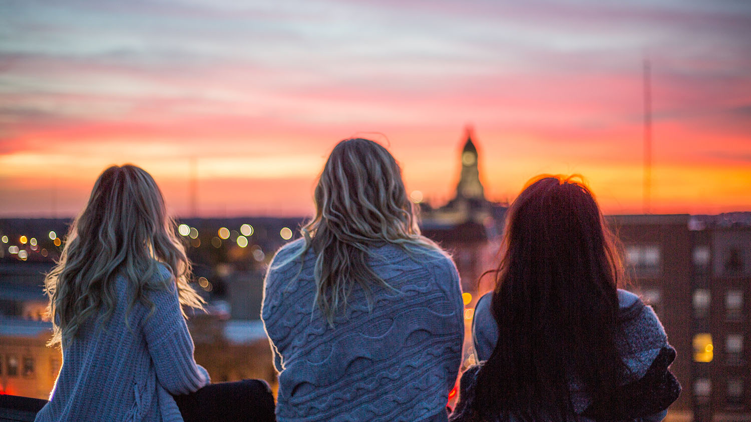 Friends on a girls getaway on a rooftop looking over the city at the sunset.