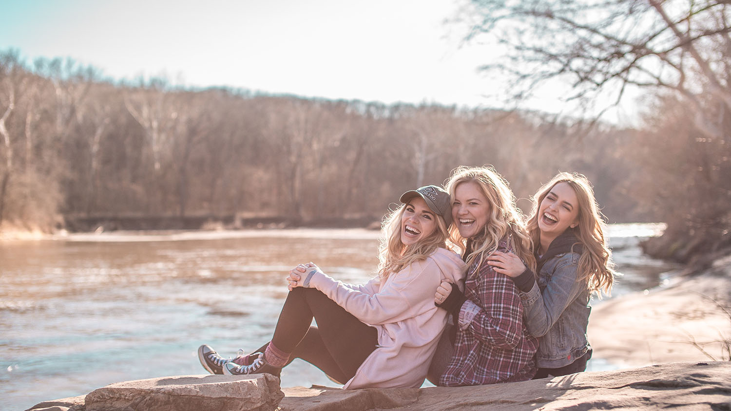 Girls laughing on a river bank enjoying the outdoors on a girls trip.
