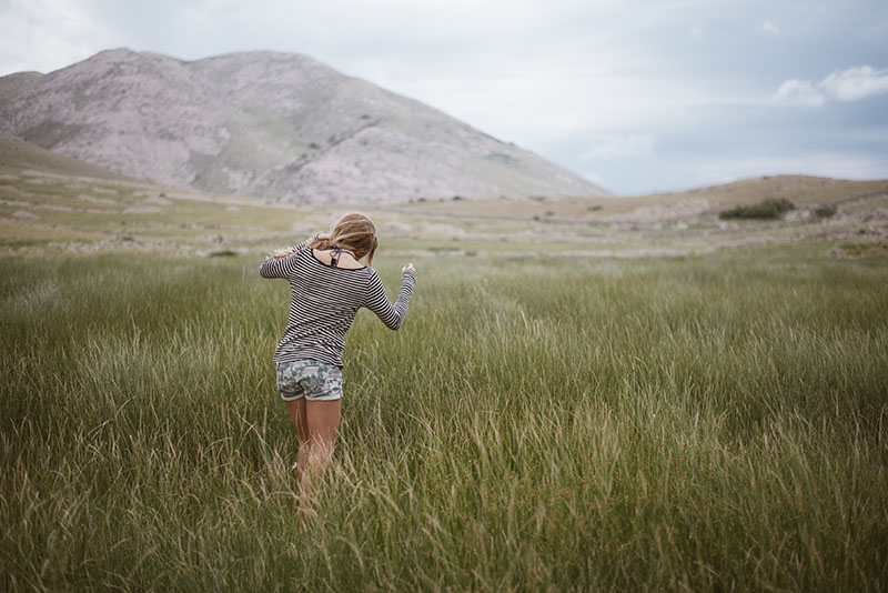 Girl walking through the grass with a mountainous background