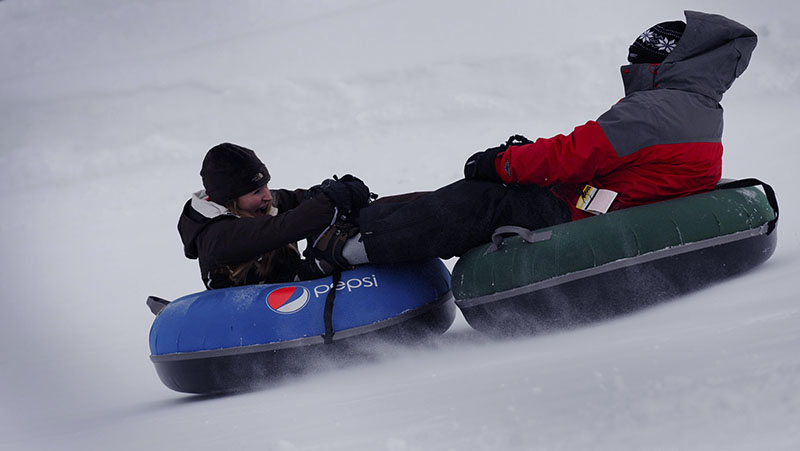Kids snow tubing down a slope at Bogus Basin Mountain Recreation Area in Boise, Idaho