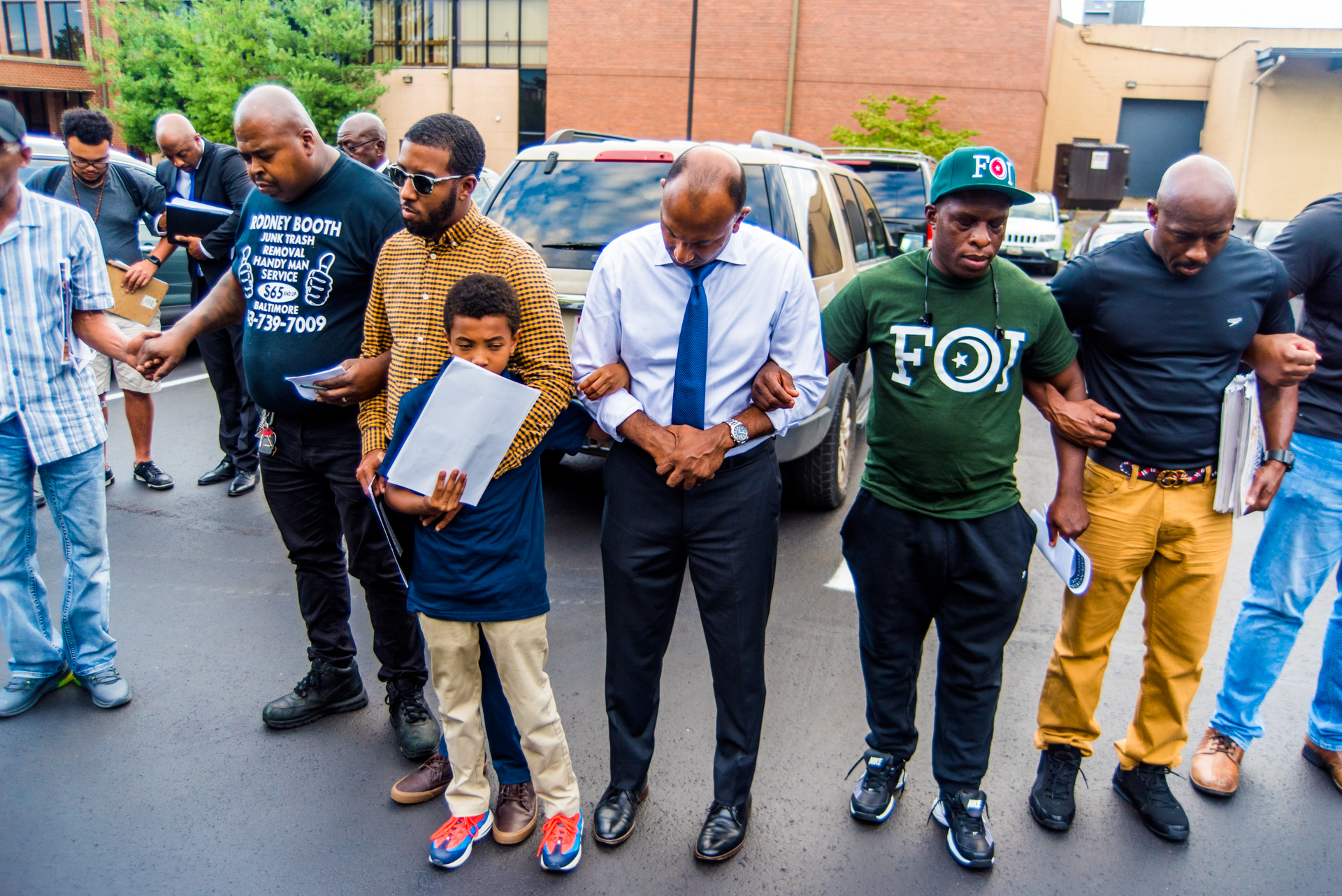 Thiru Vignarajah stands center, arms linked with other men in a prayer circle as they prepare to march down the streets of Baltimore to speak with corner boys