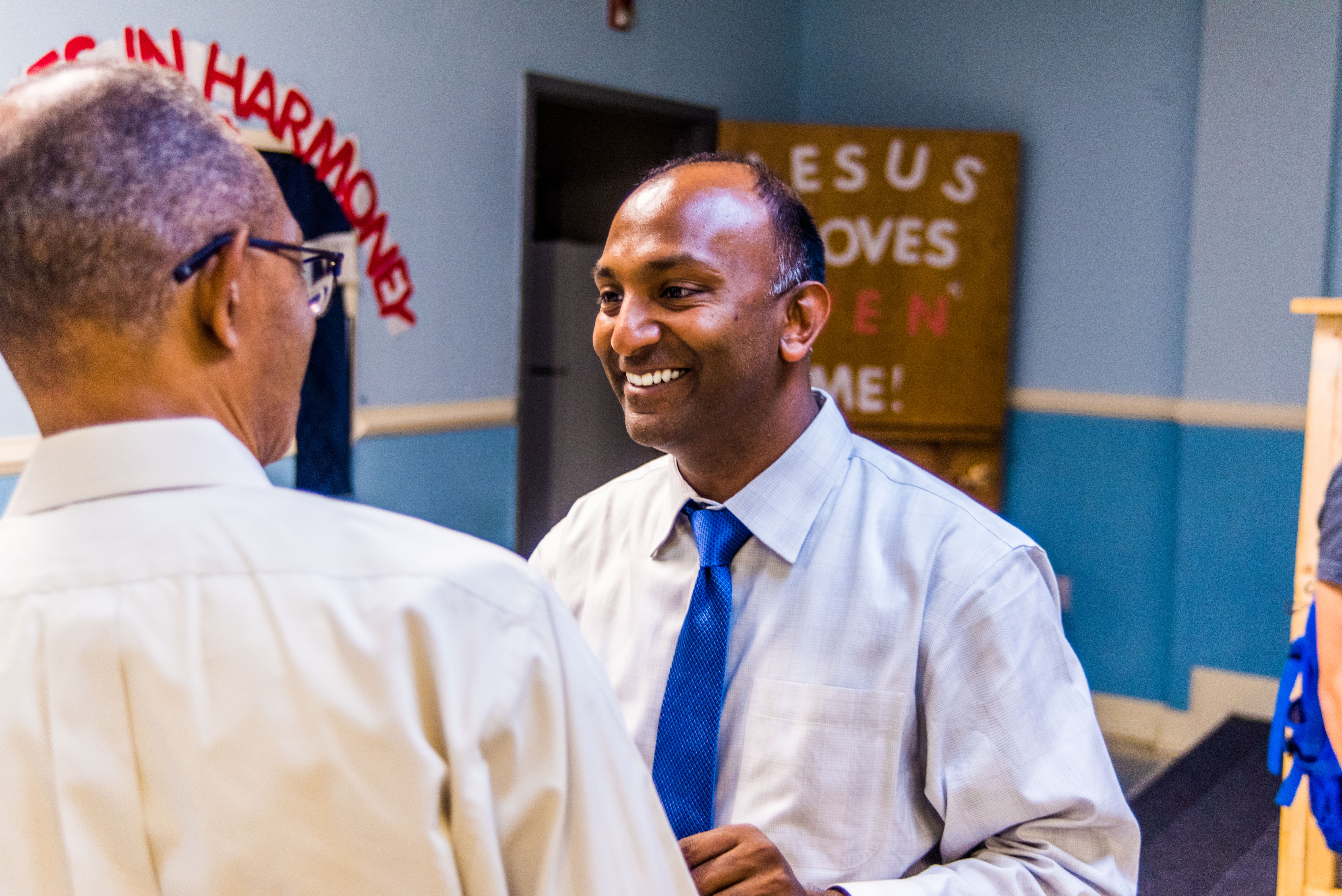 Thiru Vignarajah smiling as he speaks with an attendee at an Edmondson Village Community Association meeting