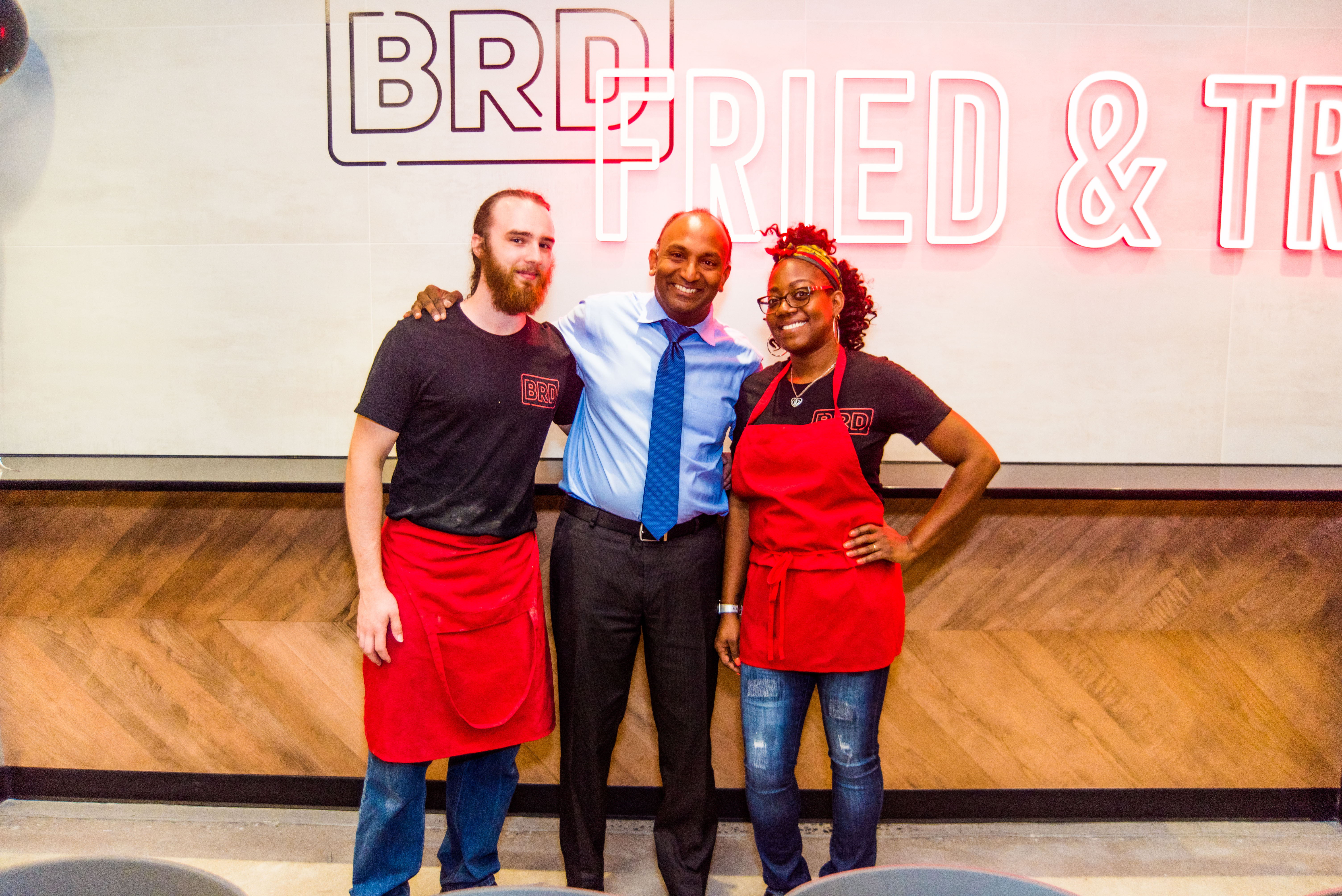 Thiru Vignarajah stands with two employees at BRD restaurant in Federal Hill