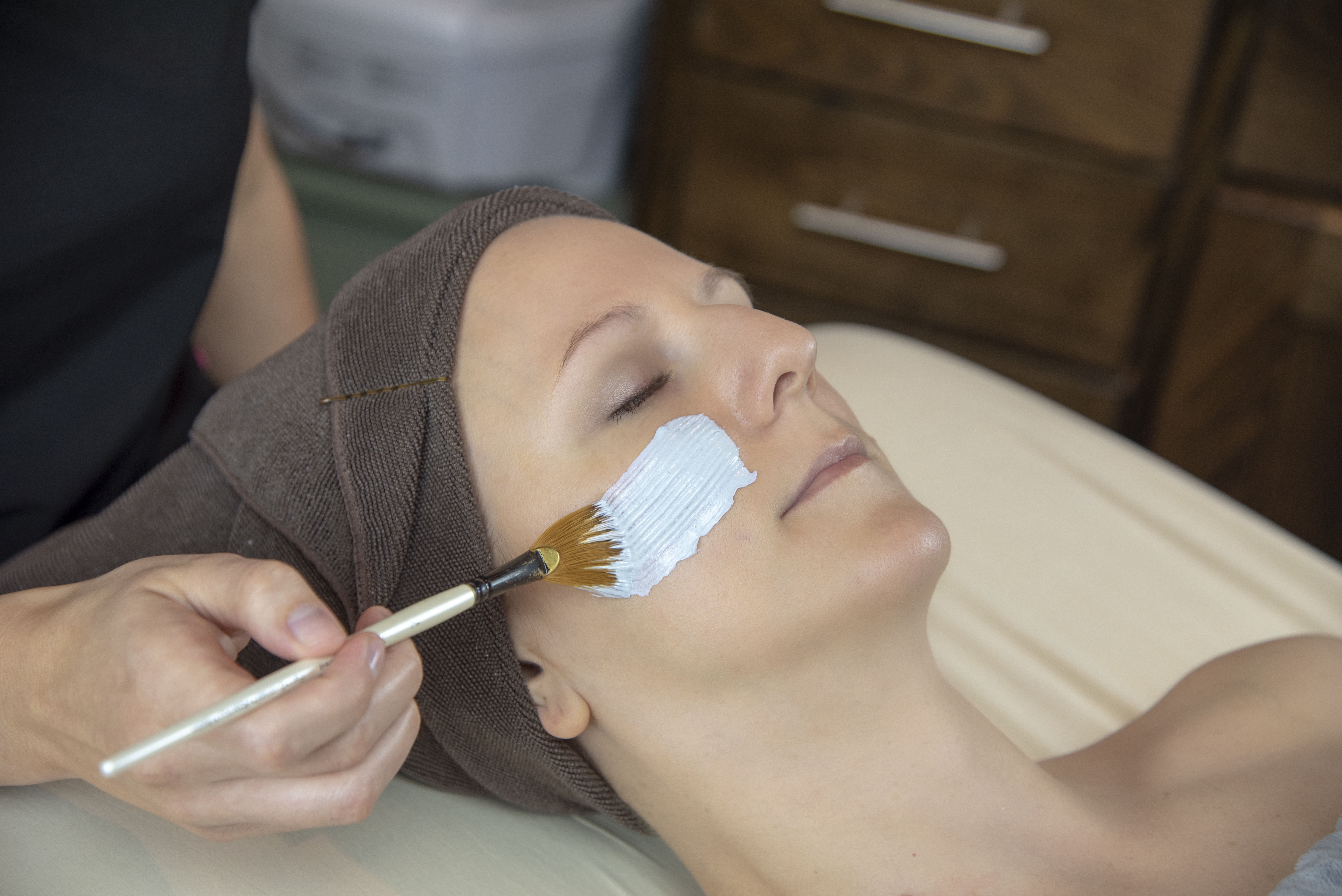 Woman with Head Wrapped in a Towel Getting a Facial