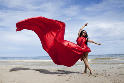 Beautiful woman with a red scarf on the beach
