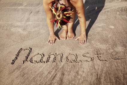 Woman doing yoga on the beach near Namaste handwriting in Goa, India