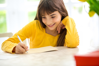 smiling girl writing a letter sitting at desk