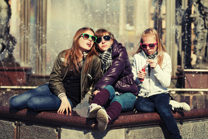 Group of teenage school girls against a city fountain