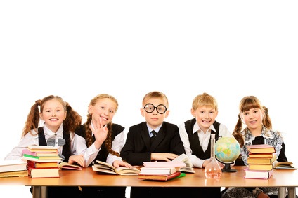 Schoolchildren sitting together at the table and engaged in lessons. Isolated over white.