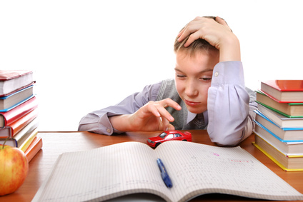 Bored Kid plays with a Toy on the School Desk on the white background