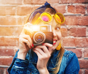 smiling girl with vintage camera taking photo with flash on brick wall background