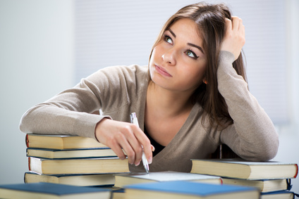 Tired student sitting with many books, with her head in hand.