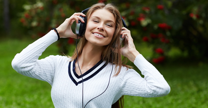portrait of woman listening to music outdoors