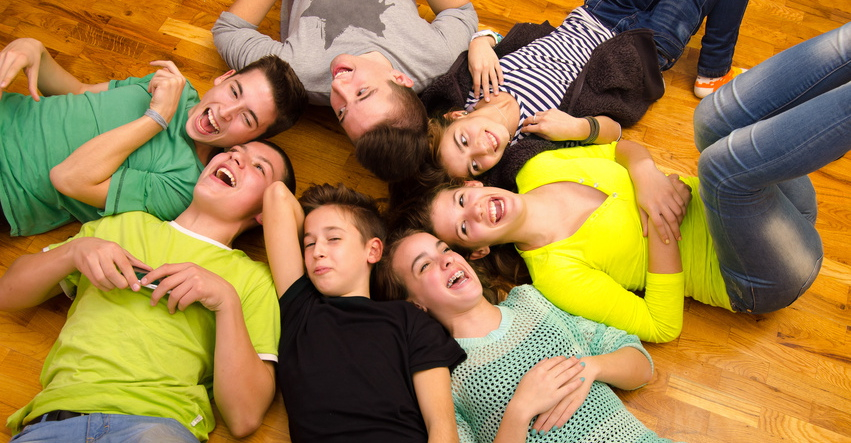 Teenage friends lying on the floor and laughing.