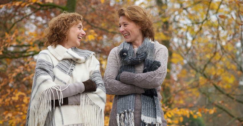 Two women smiling at each other with an yellow autumn background