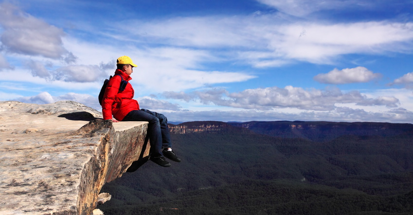Sitting on Top of the World - hiker rests and admires views of Blue Mountains on a beautiful sunny day.