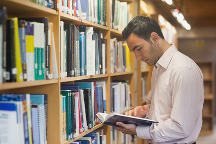 Intellectual man reading a book standing in library in front of bookshelves