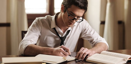 Writer at work. Handsome young writer sitting at the table and writing something in his sketchpad