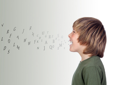 Adorable preteen with many letters out of his mouth isolated on a over grey background