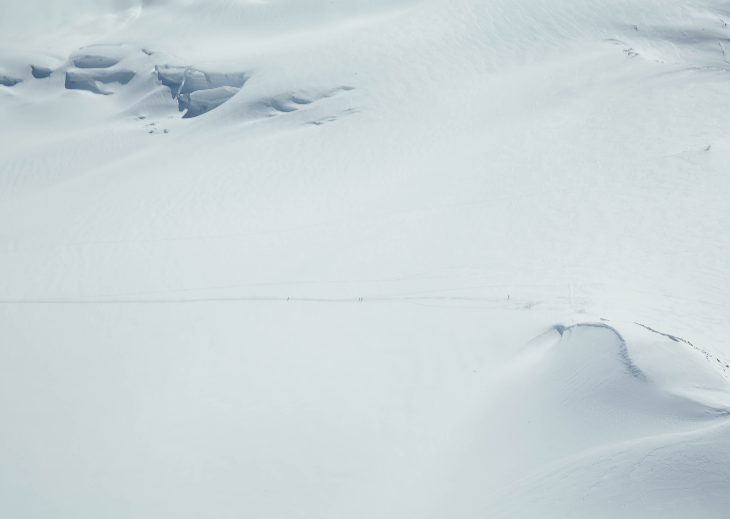 Skiers traversing across a snowy mountain in British Columbia Canada.