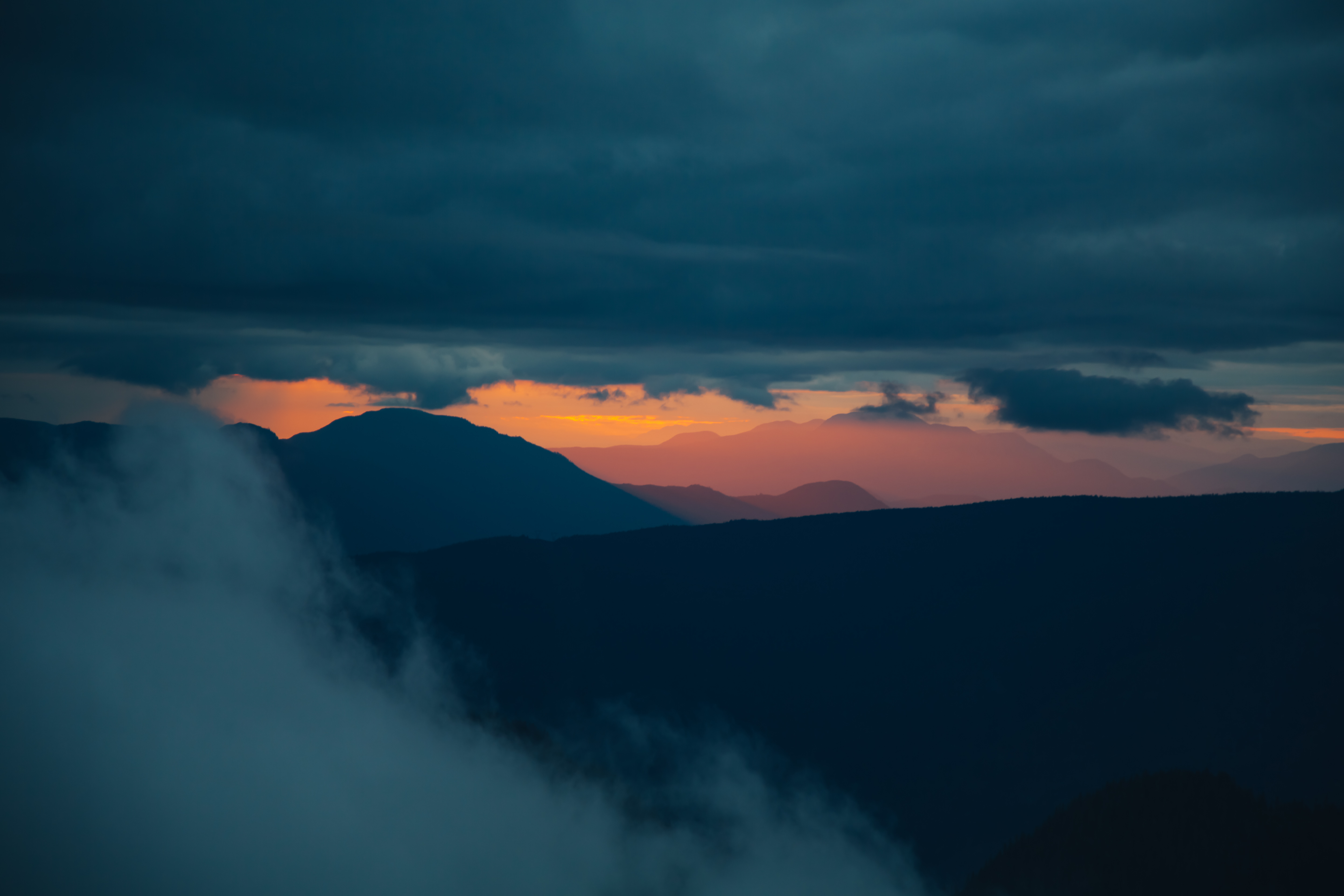 Sunset over the mountains, a dark and moody landscape.