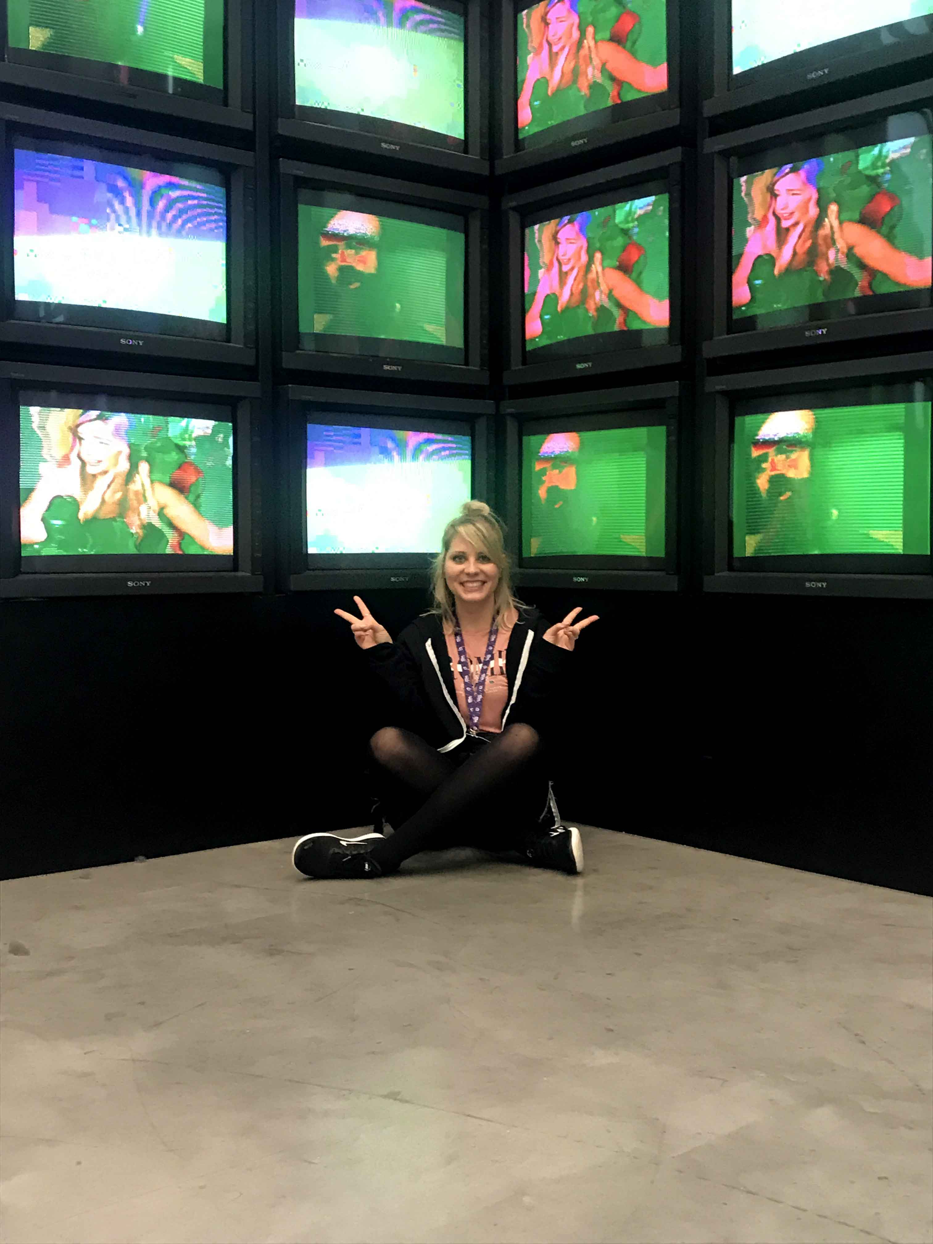 CEO Kat sat on the floor with TVs