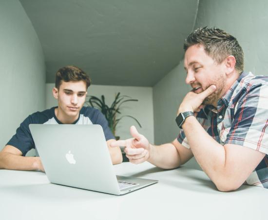 un professeur aide un étudiant sur un ordinateur