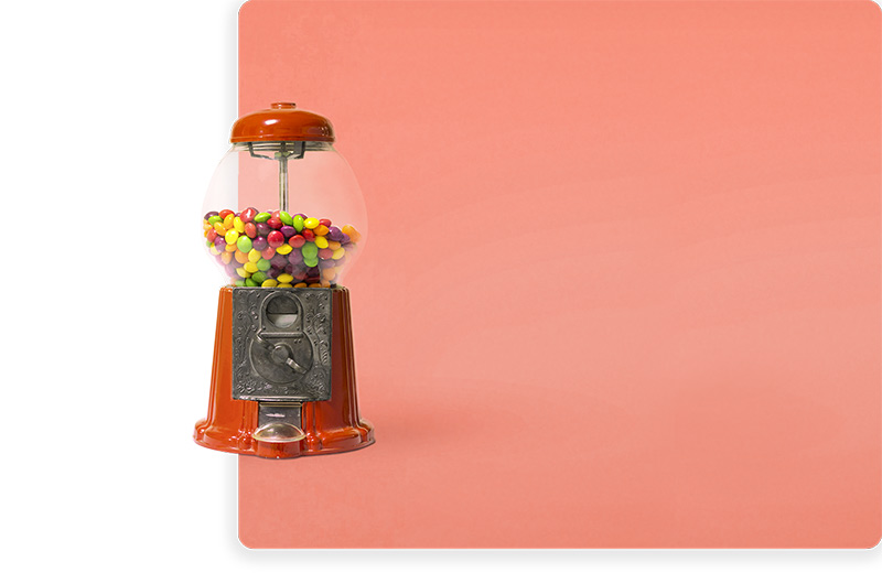 Photo of a candy dispenser on a coral background