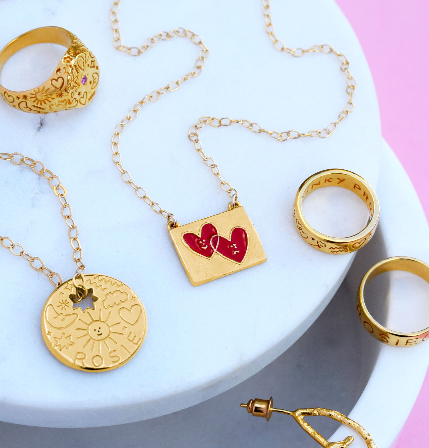 Collection of gold jewellery pieces covered in doodle-style illustrations.