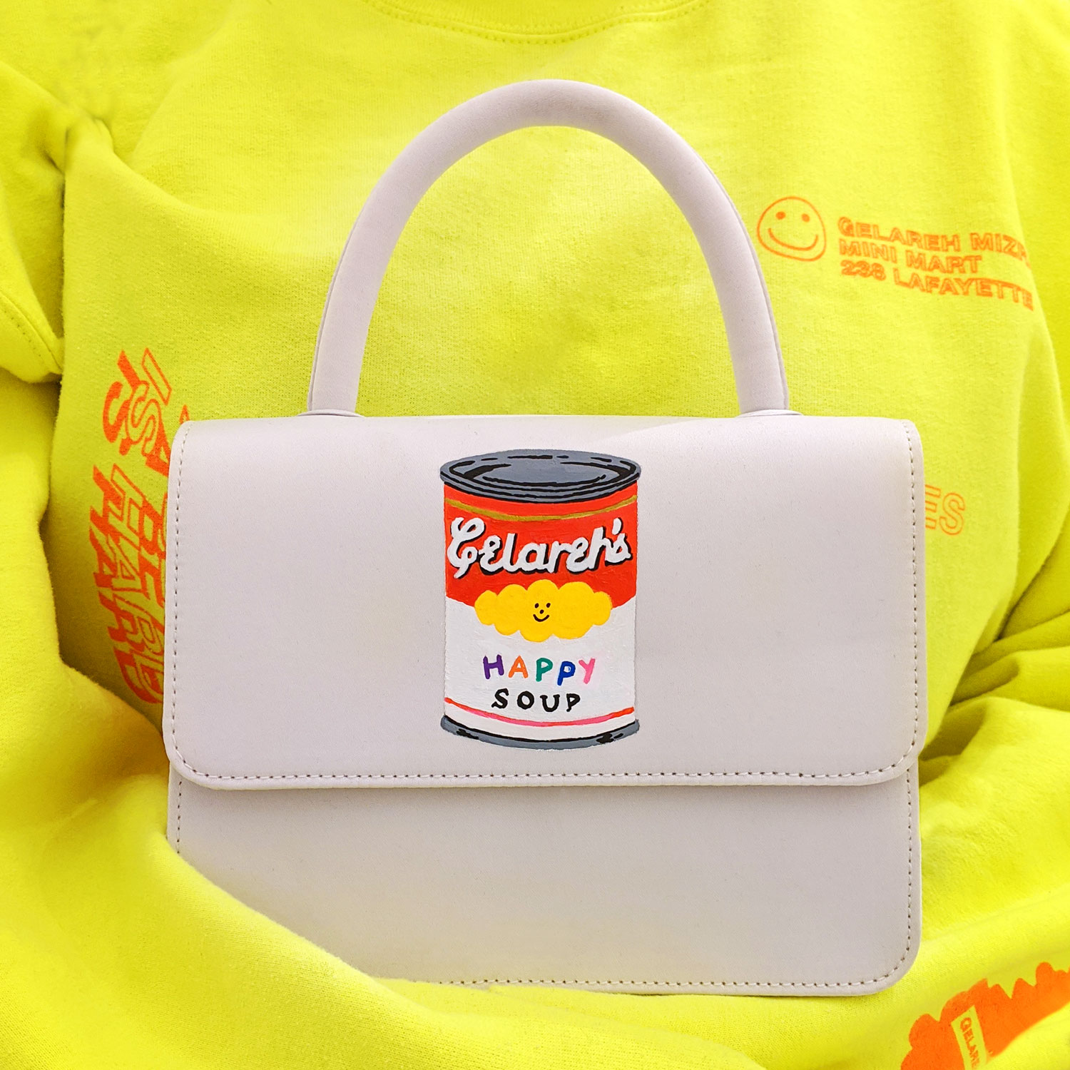 White satin hand-bag painted with an illustration of a can reading: 'Gelareh's Happy Soup'