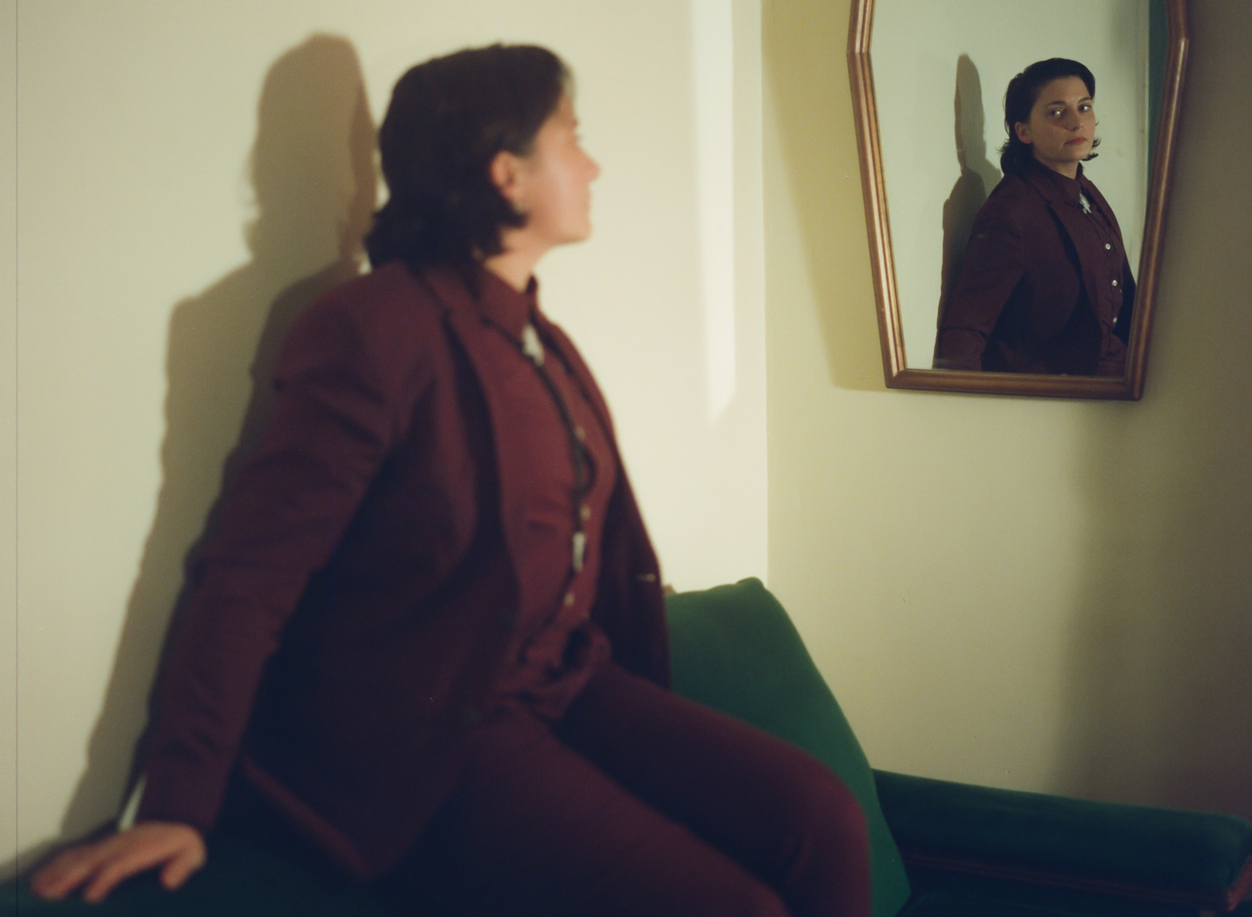 Rosie dressed in all an maroon suit, seated on a bench, looking into a coffin shaped mirror where you see their face reflected