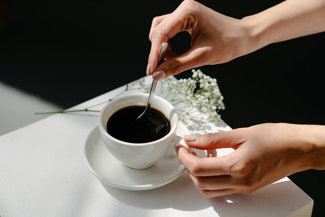 Anonymous woman stirring coffee near twigs