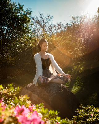 A woman meditating while in a garden