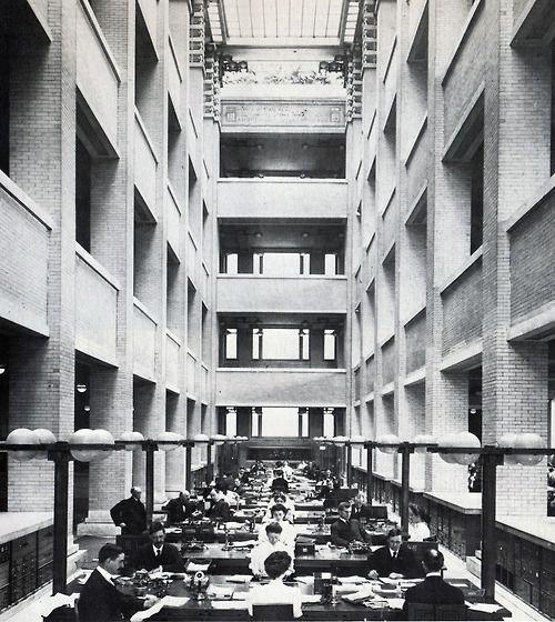 Symetryczne miejsca pracy w symetrycznym biurowcu przypominającym świątynię