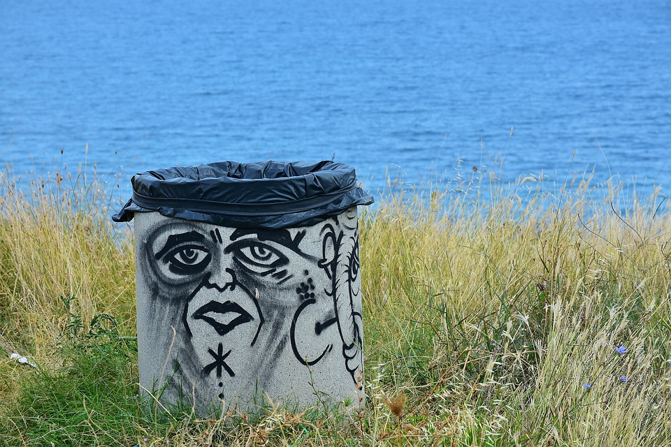 Trash can covered in graffiti of sad face