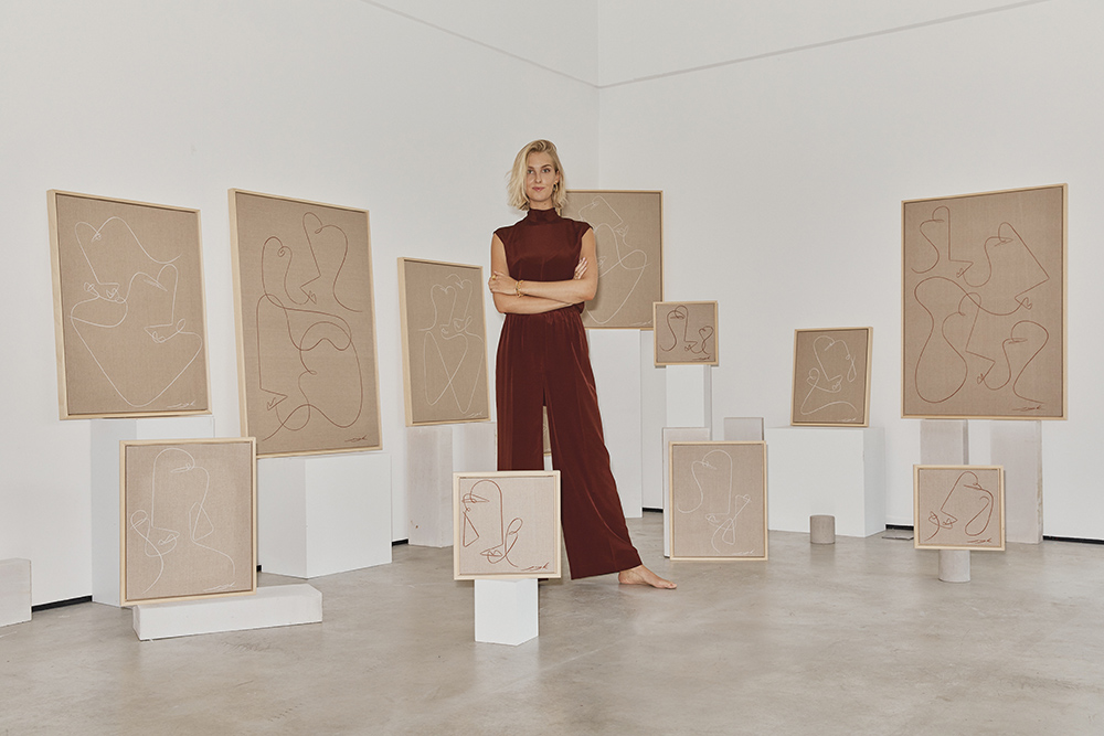 Jessica Kaye standing with her collection 'Here & There'