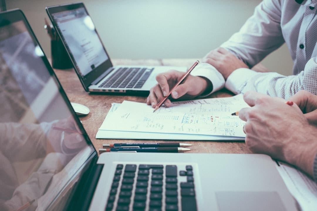 Ideeën bespreken achter een bureau, om samen tot een goed plan of ontwerp te komen voor een website