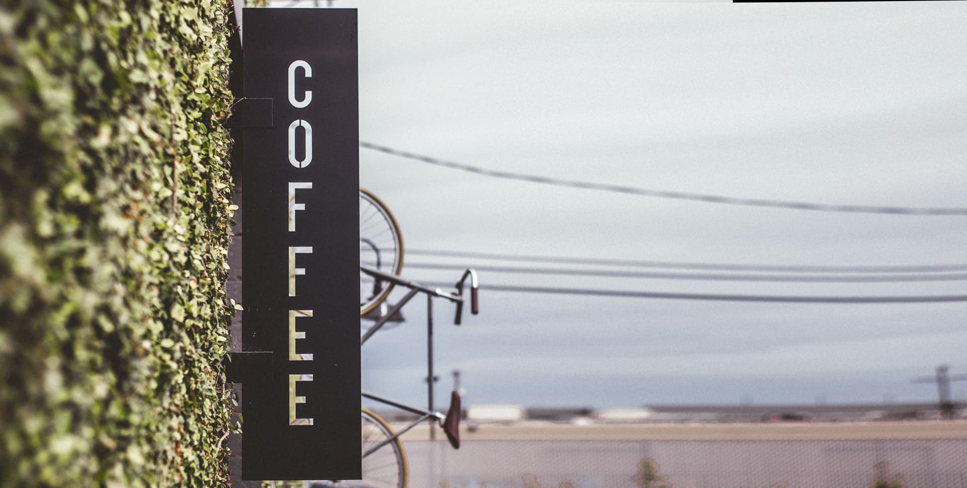 "Outdoor shot focused on the ""coffee"" sign of Common Room Coffee shop."