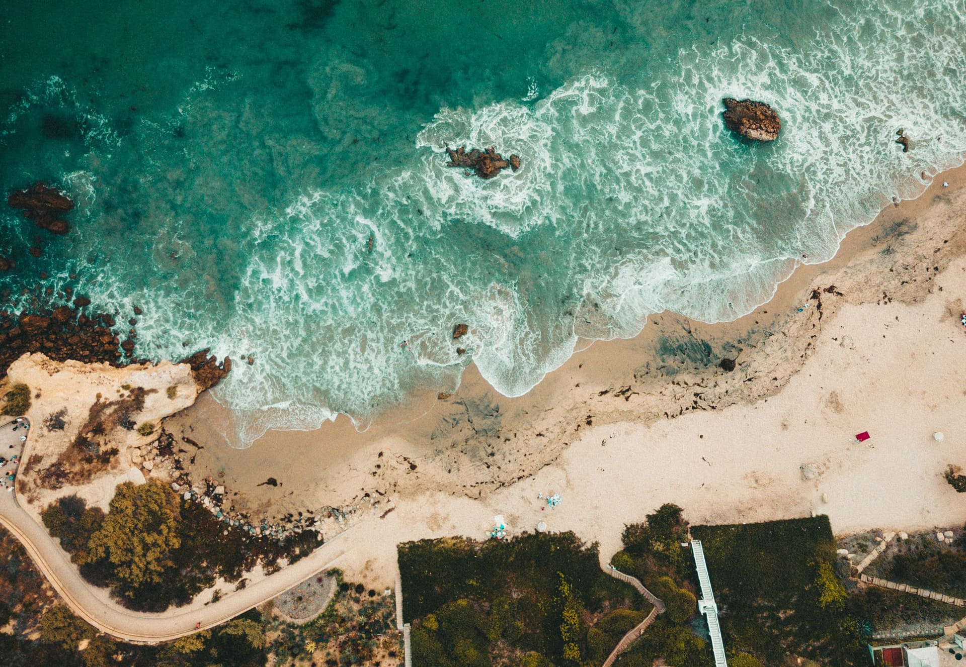 Areal shot of a secluded sandy beach with waves crashing.