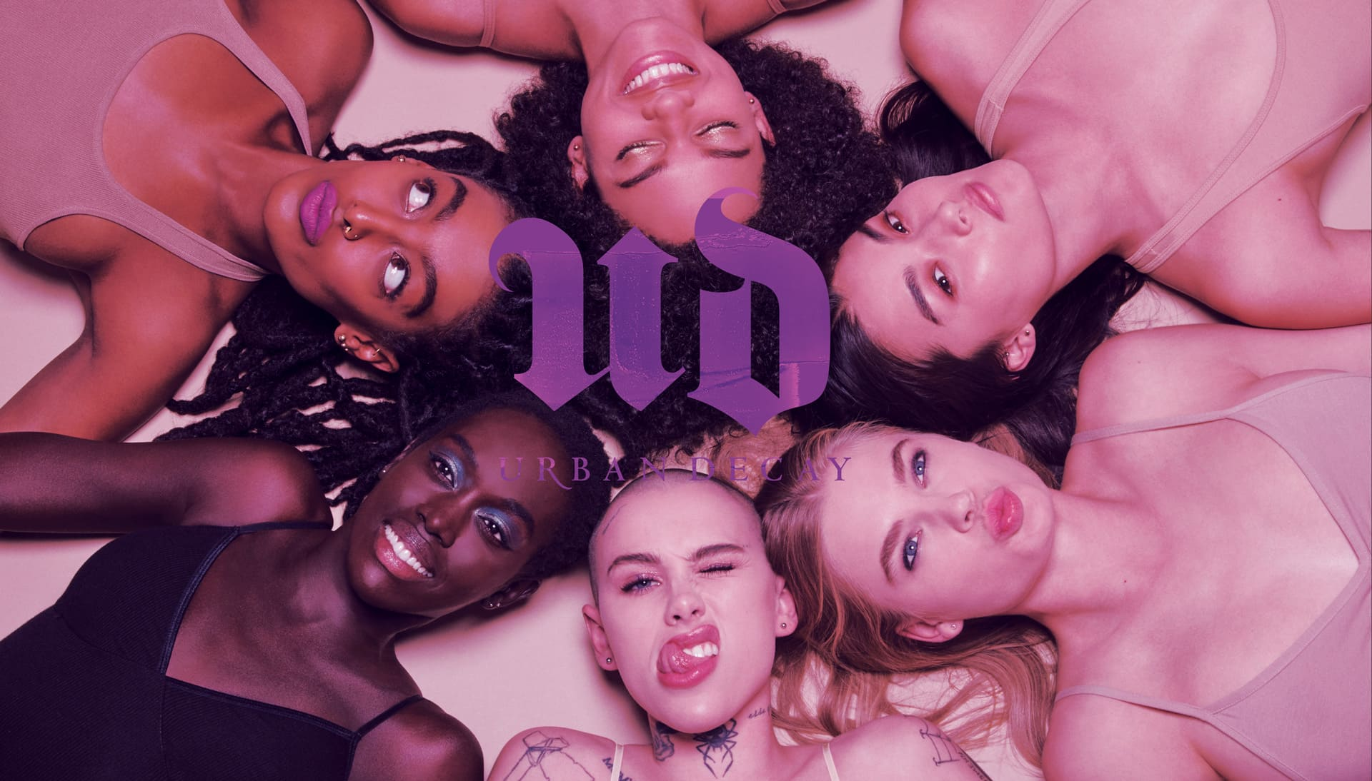 A diverse group of 6 women lying in a circle around the Urban Decay logo.