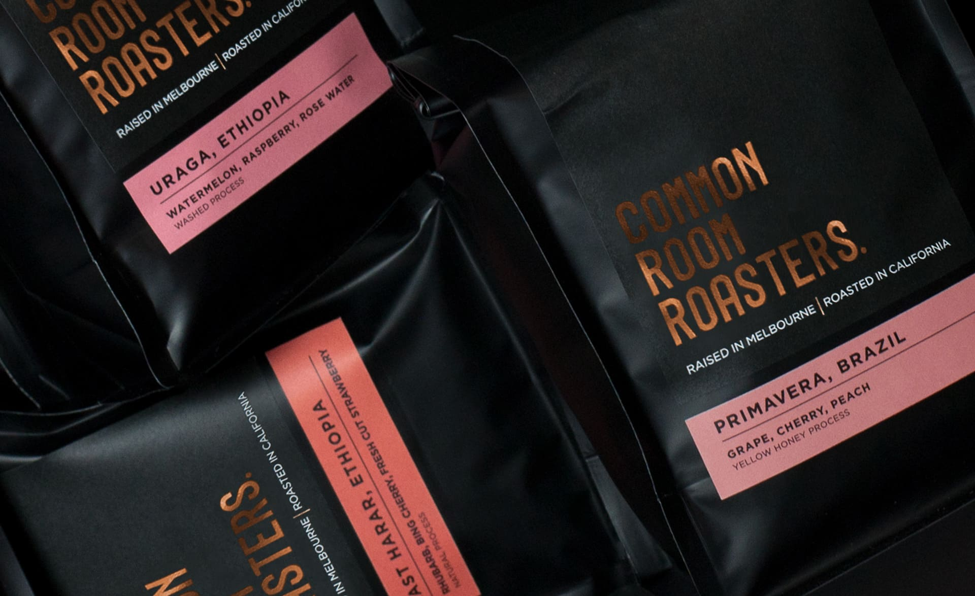 Top-down shot of three black Common Room Roasters coffee bags.