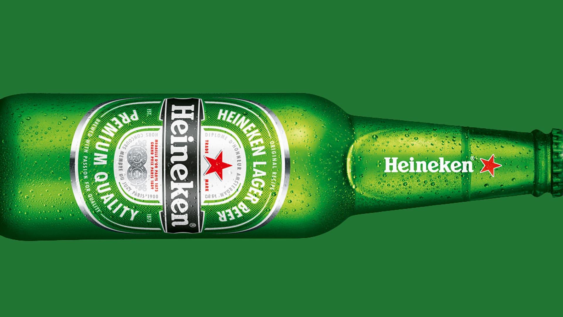Green Heineken bottle laid horizontally on a green background.