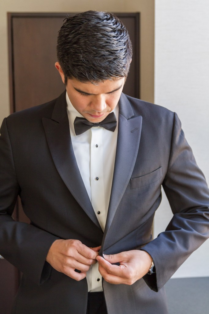 Groom in classic black suit and bowtie getting ready