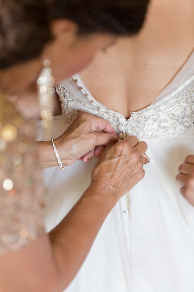 Mother of the bride helping bride with her dress
