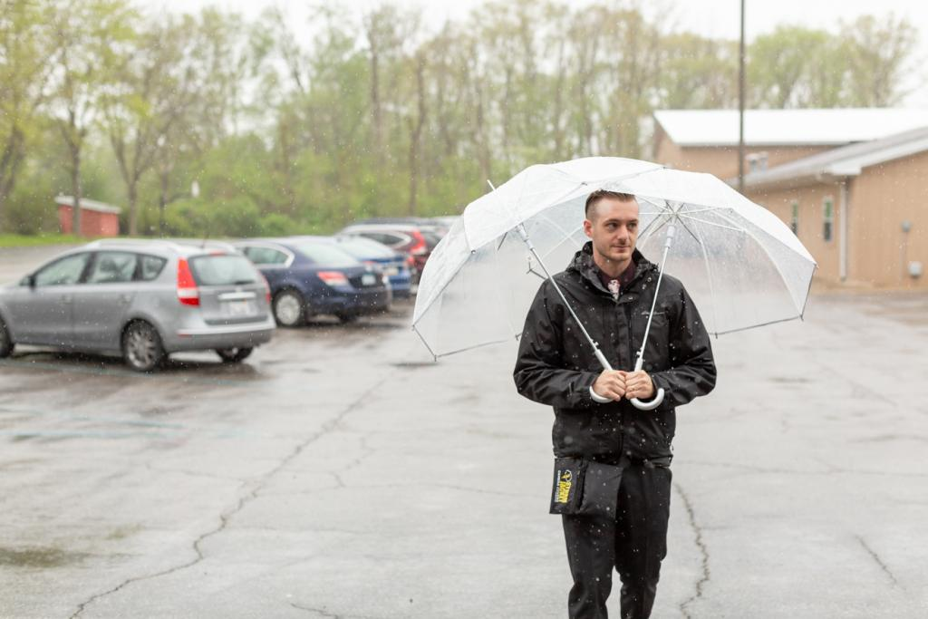 Brave photographer taking on the elements on a rainy wedding day.