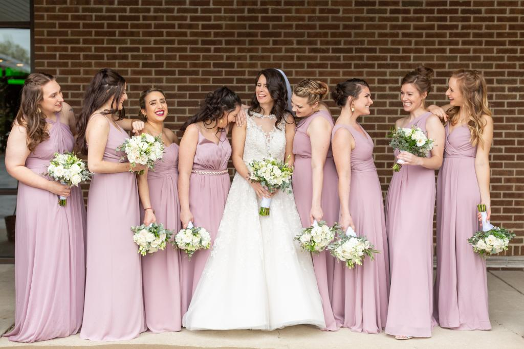 Bride having fun with her bridesmaids in pink dresses