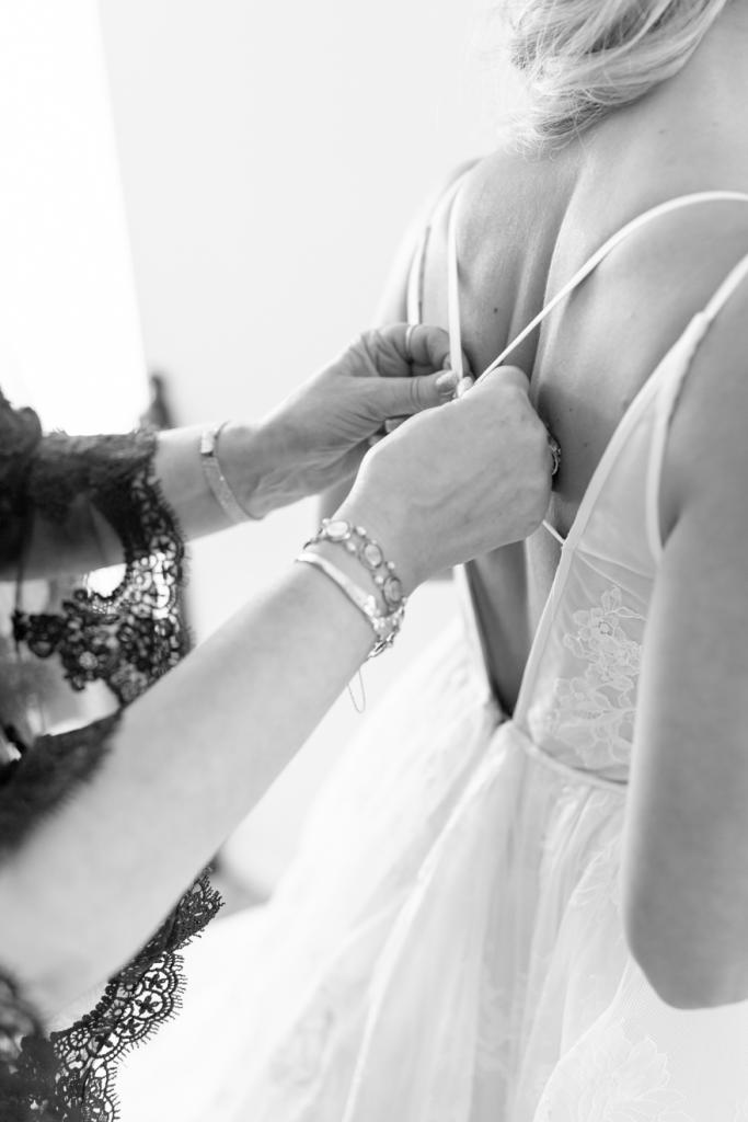 Mother of the bride helping her daughter into her dress