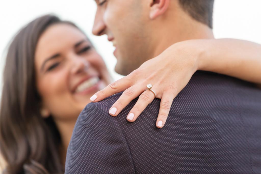 Engagement ring on maroon jacket